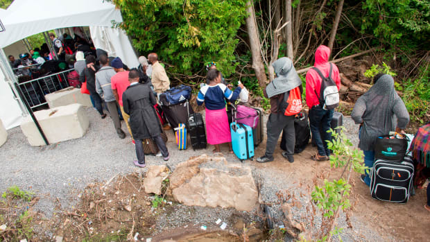 A long line of asylum seekers wait to illegally cross the Canada/U.S. border.