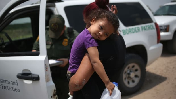A mother and child await transport to a processing center for undocumented immigrants on July 24th, 2014, in Mission, Texas.