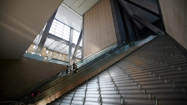 Office workers ride an escalator in the lobby of the Hearst Tower, the first building in New York to get LEED certification.