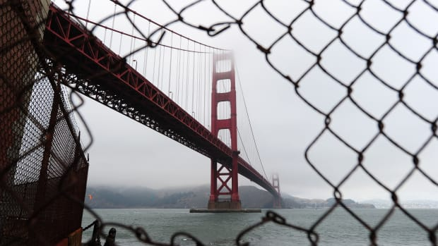 A view of the Golden Gate Bridge is seen through a hole in a fence closing off a part of Fort Point in San Francisco.