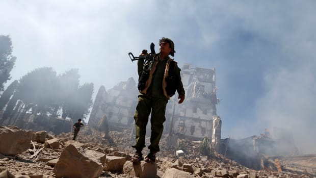 Huthi rebel fighters inspect the damage after a reported air strike carried out by the Saudi-led coalition.