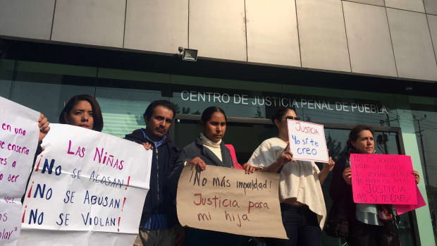 Sonia Escobar (center) stands with activist Natali Arias (left) and other supporters on the first day of her daughter's hearing at the Centro Justicia Penal in Puebla, Mexico, on April 30th, 2018.
