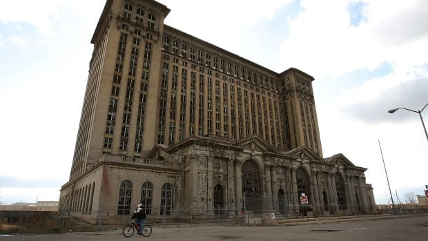 A man rides his bike past the shuttered Michigan Central Railroad Station November 20th, 2008, in Detroit, Michigan.