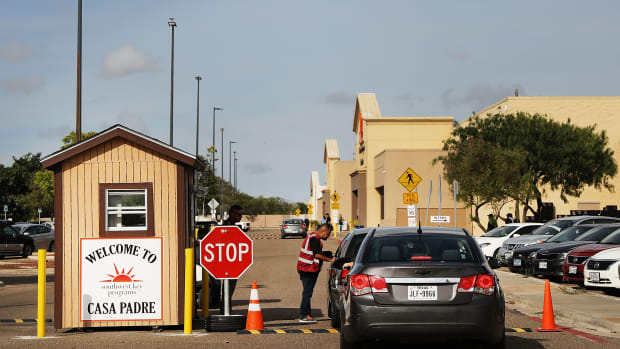 A security guard checks cars at the entrance to Casa Padre, a former Walmart that is now a center for unaccompanied immigrant children, on June 24th, 2018, in Brownsville, Texas.