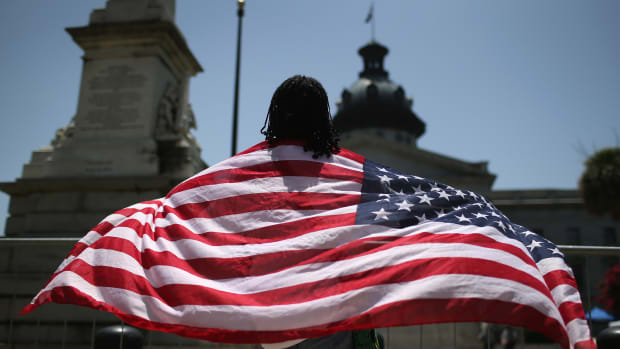 Brenda Brisbon wears the 'Stars and Stripes' after the Confederate 'Stars and Bars' was lowered from the flagpole in front of the statehouse on July 10th, 2015, in Columbia, South Carolina.