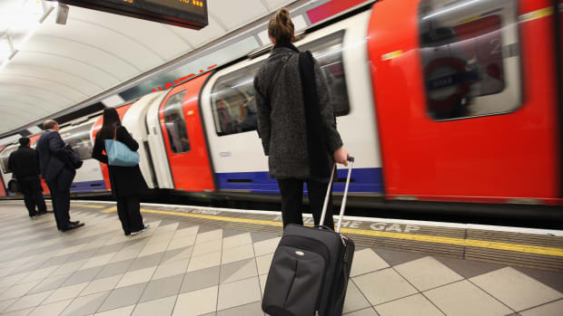 Commuters wait for a train at a London Underground station.