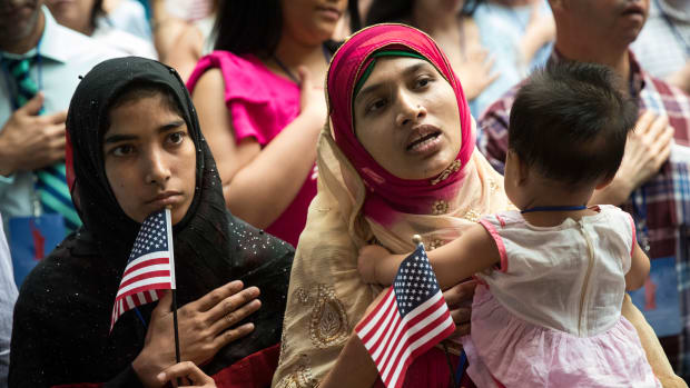 New United States citizen Mosammat Rasheda Akter, originally Bangladesh, holds her seven-month-old daughter Fahmida as she sings the U.S. National Anthem during naturalization ceremony at the New York Public Library on July 3rd, 2018, in New York City. Two hundred immigrants from 50 countries became citizens during the ceremony.