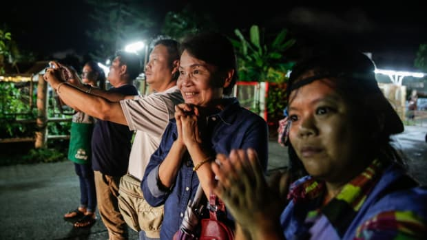 Onlookers cheer as ambulances deliver boys rescued from a cave in northern Thailand to a hospital on July 8th, 2018, in Chiang Rai, Thailand. Divers began an effort to pull the 12 boys and their soccer coach on Sunday morning after they were found alive in the cave in northern Thailand.