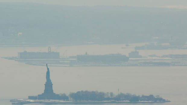 A hazy smoke hangs over Liberty Island after a storage facility explosion in nearby Staten Island February 21st, 2003 in New York.