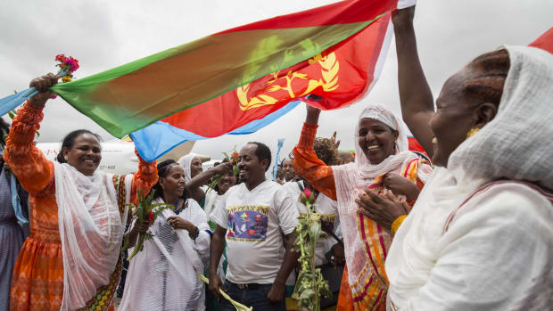Eritrean women hold up their nation's flag on July 18th, 2018, to welcome passengers on the flight from Ethiopian capital Addis Ababa at Asmara International Airport.