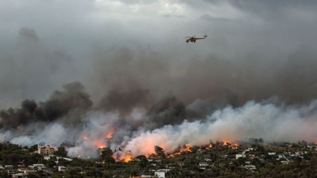A firefighting helicopter flies over a wildfire raging in the town of Rafina near Athens, on July 23rd, 2018. At least five people have died and more than 20 have been injured as wildfires tore through woodland and villages around Athens on Monday, while blazes caused widespread damage in Sweden and other northern European nations.