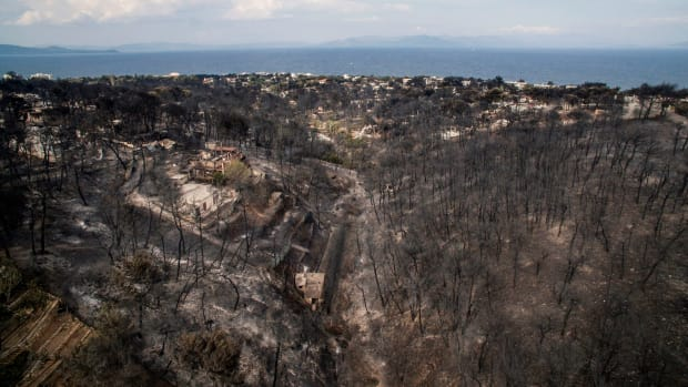 An aerial view shows damage caused by a wildfire near the village of Mati, near Athens, on July 24th, 2018. More than 70 have died and 170 have been injured in wildfires ravaging woodland and villages in the Athens region. The death toll soared with a Red Cross official reporting the discovery of 26 bodies in the courtyard of a villa at the seaside resort of Mati.