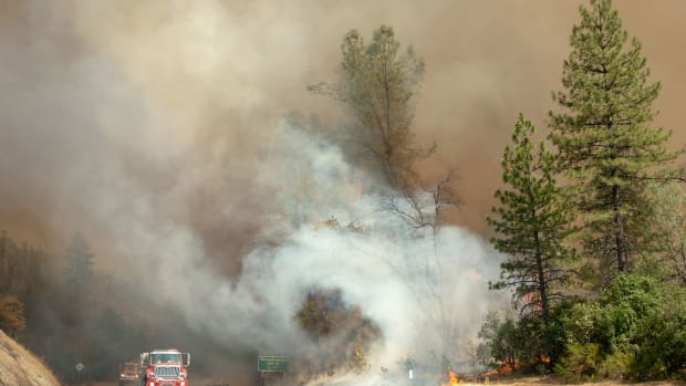 Fire trucks pass by approaching flames during the Carr fire near Whiskeytown, California, on July 27th, 2018.