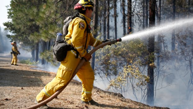A firefighter extinguishes flames while battling the Carr fire on July 30th, 2018, near Redding, California.