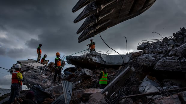 An Indonesian search-and-rescue team looks for victims under a collapsed mosque following an earthquake on August 7th, 2018, in Lombok Island, Indonesia. Nearly 100 people have been confirmed dead and at least 20,000 people have been left homeless after the 6.9 magnitude earthquake hit Lombok and neighboring Bali.