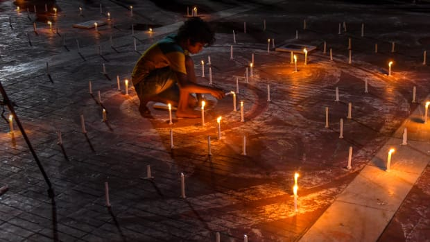 A Bangladeshi child lights a candle to mark International Day of the World's Indigenous Peoples in Dhaka on August 8th, 2018. International Day of the World's Indigenous Peoples takes place on August 9th to promote and protect the rights of indigenous communities and cultures.