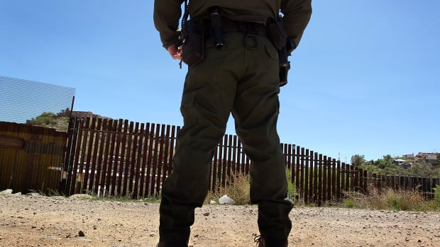 A U.S. Border Patrol agent stands near the border fence between the United States and Mexico in Nogales, Arizona.
