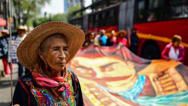 People from San Salvador Atenco, a town outside of Mexico City, protest the construction of a new international airport on August 14th, 2018. For years, residents of the semi-rural town have fought against plans to construct the the Mexican capital's new airport adjacent to their town, fearing that the construction will result in their displacement. On Tuesday, protesters sought to pressure President-Elect Andrés Manuel López Obrador to commit to his campaign promise to cancel the airport's construction (the president-elect has since vacillated on the promise). In this photo, a woman holds a machete and marches in front of a banner bearing the image of Emiliano Zapata, a hero of the Mexican Revolution who famously sought to return land rights to indigenous people in the country's south.