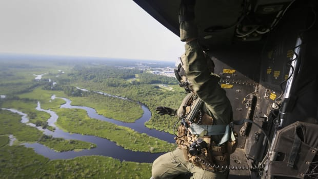 A crew chief with Marine Light Attack Helicopter Squadron 167, 2nd Marine Aircraft Wing, rides in the back of a UH-1Y Venom as it approaches a landing zone during a training exercise near Camp Lejeune, North Carolina, on June 17th, 2016.
