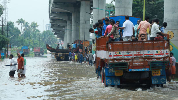 Indian commuters travel in a truck to a safer place as flood waters ravage the National Highway 47 in the Ernakulam district of Kochi, in the Southern Indian state of Kerala, on August 16th, 2018. According to the BBC, the death toll from floods in Kerala rose to over 100 on August 16th as torrential rainfall threatened new areas.