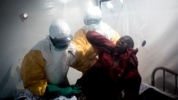 An Ebola patient is lifted up by two medical workers after being admitted into a Biosecure Emergency Care Unit (CUBE) on August 15th, 2018, in Beni, Democratic Republic of the Congo.