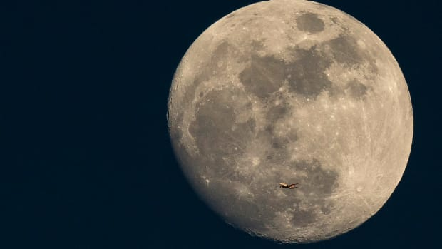 A plane flies past the moon at sunset on March 3rd, 2015 in London, England.