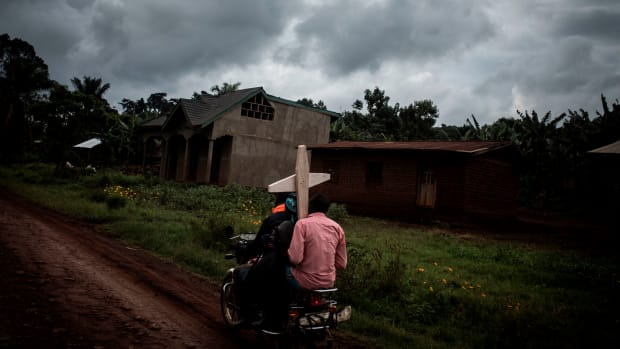 People carry a cross for a grave on August 23rd, 2018, in Mangina, North Kivu province, DRC.