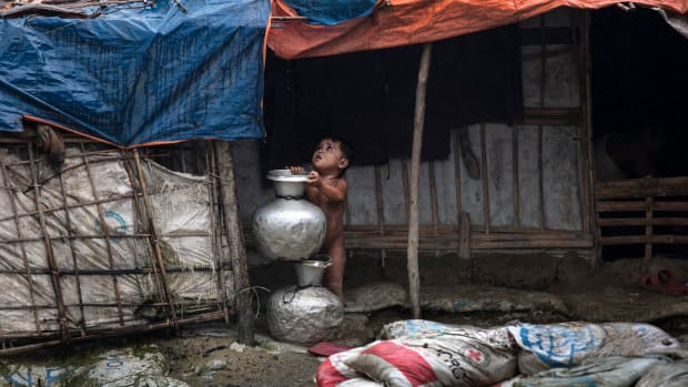 A young child stands under a shelter as monsoon rains hit on August 28th, 2018, in Unchiprang refugee camp, Cox's Bazar, Bangladesh. Tuesday marked the one-year anniversary since a wave of violence forced more than 720,000 Rohingya to flee into the Cox's Bazar district. United Nations investigators said on Monday that Myanmar's army had carried out genocide against the Rohingya in Rakhine state, and that its top military figures must be investigated for crimes against minorities across the country. The U.N. report accused Myanmar's military of murders, imprisonments, enforced disappearances, torture, rape, and other forms of sexual violence in Rakhine state, all of which constitute crimes against humanity.