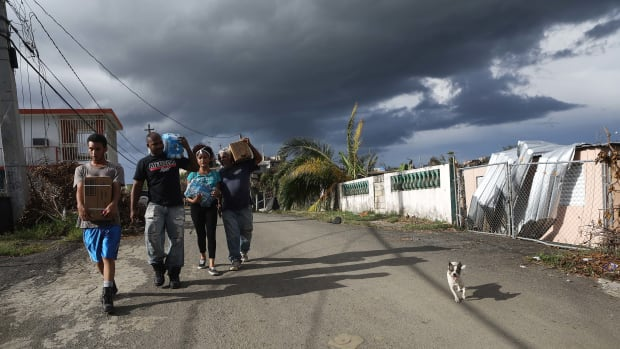 Puerto Rican residents carry water and Meals-Ready-to-Eat received from FEMA about two weeks after Hurricane Maria swept through the island, on October 5th, 2017, in San Isidro, Puerto Rico.