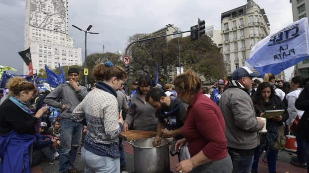 Volunteers prepare a free meal at a soup kitchen along 9 de Julio Avenue in Buenos Aires, backdropped by a portrait of Eva Peron on the wall of the Social Development and Health Ministry building, on September 12th, 2018, during a protest against the government of Argentine President Mauricio Macri. Argentinian social organizations are demanding the declaration of a food emergency amid a financial crisis that has increased in recent months. On Wednesday, demonstrators gave away food rations as a means of protesting the government.