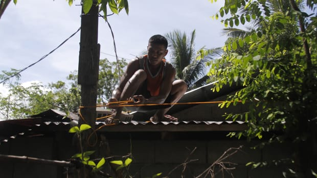 A resident secures the roof of his house to a tree in preparation for Super Typhoon Mangkhut in Candon City, Ilocos Sur province, north of Manila, on September 13th, 2018. The super typhoon, a Category 4 storm, roared toward the Philippines on September 13th, packing fierce winds and heavy rains that are expected to strike the disaster-prone nation during the weekend before moving on to China.