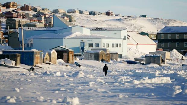 A man walks along the shoreline in Iqaluit, Canada, in February of 2010.
