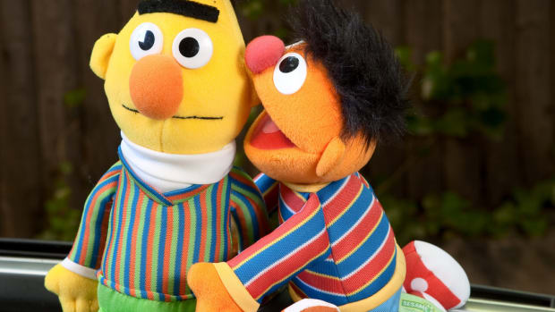 Bert whispers in Ernie's ear on Sesame Street.
