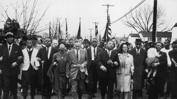 Martin Luther King and Coretta Scott King lead a civil rights march in Selma, Alabama.