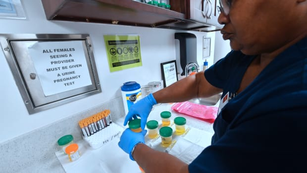 A medical assistant closes bottles of patients' urine submitted for STD testing in Hollywood, California, on May 18th, 2018.