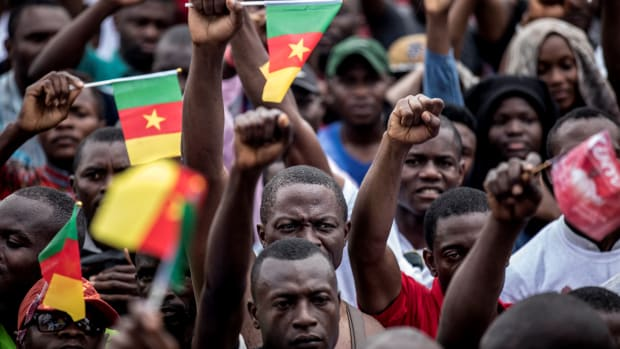 Supporters of the leader of the Cameroonian opposition party Movement for the Rebirth of Cameroon raise their fists during a campaign rally in Yaounde for the presidential elections.