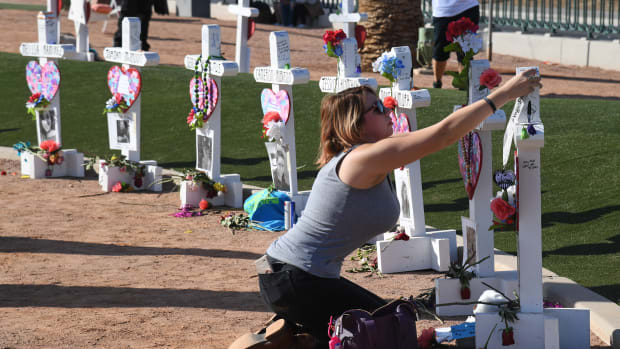 Ashley Schuck of Nevada places a medal from Saturday's Vegas Strong 5k on a cross set up for shooting victim Neysa Tonks on October 1st, 2018, in Las Vegas, Nevada. Retired carpenter Greg Zanis, who installed 58 crosses last year—one for each person killed—set up the memorial again with new crosses for the massacre's anniversary. On October 1st, 2017, Stephen Paddock opened fire on the Route 91 Harvest Country Music Festival, killing 58 people and injuring more than 800 in the deadliest mass shooting event in modern United States history.