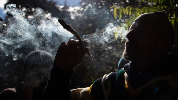 A man smokes marijuana during a legalization party at Trinity Bellwoods Park in Toronto, Ontario, on October 17th, 2018. Nearly a century of marijuana prohibition came to an end Wednesday as Canada became the first major Western nation to legalize and regulate its sale and recreational use. Scores of customers braved the cold for hours outside Tweed, a pot boutique in St John's, Newfoundland, that opened briefly at midnight, to buy their first grams of legal cannabis. In total, Statistics Canada says 5.4 million Canadians will buy cannabis from legal dispensaries in 2018—about 15 percent of the population. Around 4.9 million already smoke marijuana.