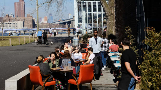 People eat outside in a Brooklyn neighborhood.