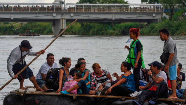Honduran migrants taking part in a caravan heading to the United States cross the Suchiate River, a natural border between Guatemala and Mexico, in a makeshift raft, in Ciudad Tecun Uman, Guatemala, on October 20th, 2018.