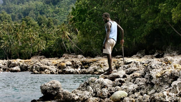 A villager looks over a coral reef in the Solomon Islands.