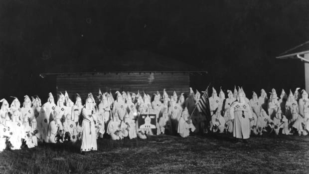 A meeting of hooded members of the Ku Klux Klan circa 1920.