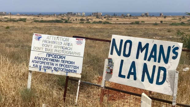 Signs mark fenced-off areas of Varosha, a quarter in the city of Famagusta, Cyprus, which until 1974 was a popular seaside resort. The buildings seen in the background are abandoned beach hotels that attracted Hollywood movie stars until the country's division.