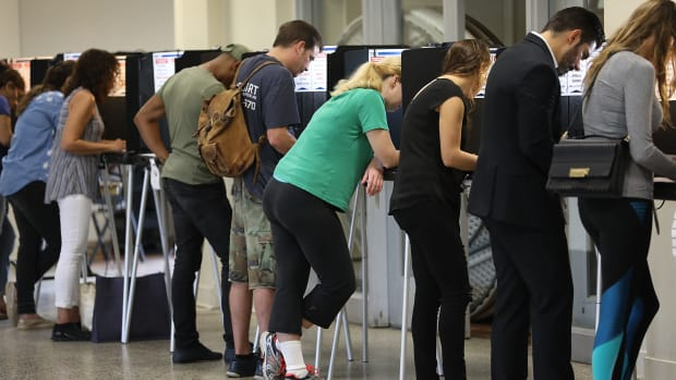 Voters fill out their ballots as they cast their vote at a polling station setup in Legion Park for the mid-term election on November 6th, 2018 in Miami, Florida.