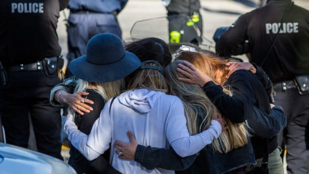 Friends hug outside the Los Robles Medical Center in Thousands Oaks, California, on November 8th, 2018, as they pay tribute to Ventura Country Sheriff's Sergeant Ron Helus, who was killed in a shooting at Borderline Bar & Grill the night before.