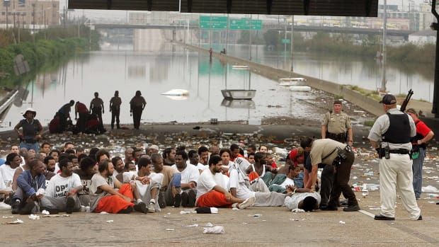 Police watch over prisoners from Orleans Parish Prison who were evacuated from their prison to the highway due to high water in New Orleans, Louisiana.