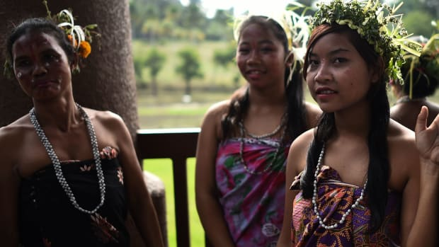 Malaysian women from the indigenous Temiar community standing backstage in traditional costume and headgear before performing during a ceremony to celebrate the International Day of the World's Indigenous Peoples in Shah Alam on the outskirts of Kuala Lumpur.