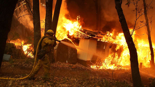 A California Department of Forestry and Fire Protection firefighter monitors a burning home as Northern California's Camp Fire moves through the area on November 9th, 2018, in Magalia, California. Fueled by high winds and low humidity, the rapidly spreading fire ripped through the town of Paradise and quickly charred 70,000 acres. It destroyed numerous homes and businesses in a matter of hours.
