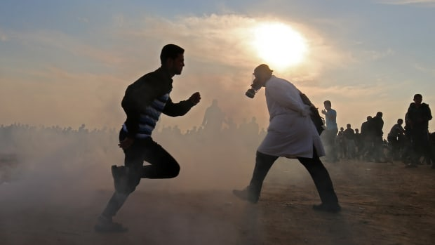 Palestinians run for cover from tear gas during clashes near the border between Israel and Khan Yunis in the southern Gaza Strip on November 9th, 2018.