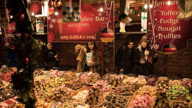 Shoppers purchase sweets from a stall at the Manchester Christmas Market, which is spread across the city center in Manchester, northern England, on November 9th, 2018.